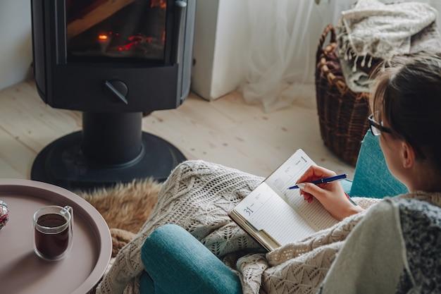 Mulher jovem escrevendo em um caderno, sentada em uma poltrona aconchegante perto da lareira