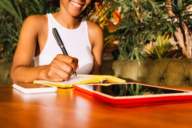 Mulher jovem, escrita, ligado, diário, com, caneta, sobre, a, tabela madeira, com, cellphone, e, tablete digital