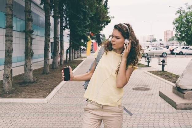 Mulher jovem, escutar música, ligado, fones