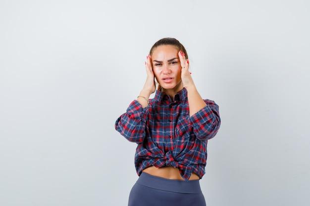 Mulher jovem esfregando as têmporas em camisa xadrez, calças e parecendo cansada. vista frontal.
