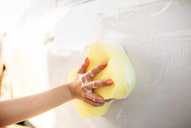 Mulher jovem esfregando veículo com espuma