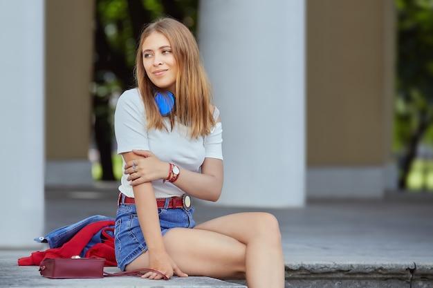Mulher jovem esguia descansa no pavilhão do jardim.