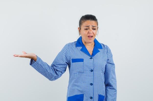 Mulher jovem espalhando a palma da mão segurando algo na camisa de pijama azul guingão e parecendo vista frontal sombria.