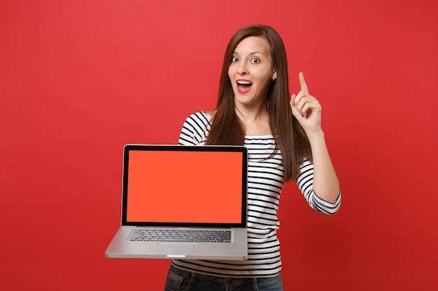 Mulher jovem espantada, apontando o dedo indicador para cima, segurando o computador laptop pc com tela vazia preta em branco, isolada no fundo da parede vermelha. emoções sinceras de pessoas, conceito de estilo de vida. simule o espaço da cópia.