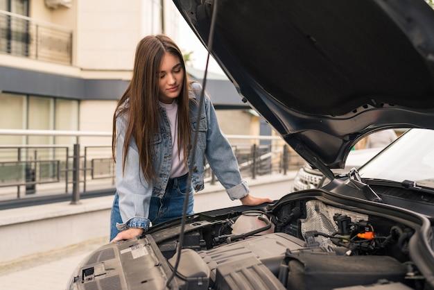 Mulher jovem espera por assistência perto de seu carro quebrado na beira da estrada.