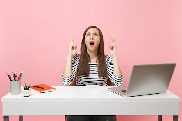 Mulher jovem espera por um momento especial com os dedos cruzados olhando para cima, sente-se no trabalho na mesa branca com um laptop pc contemporâneo