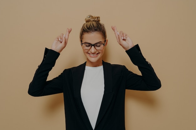 Mulher jovem esperançosa em pé com as mãos para cima e os dedos cruzados em um gesto de sorte, feminina em um blazer preto elegante com cabelo loiro amarrado em um coque bonito, fazendo desejo com os olhos fechados. linguagem corporal