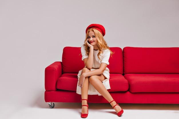 Mulher jovem espetacular com expressão de rosto feliz relaxando na sala de estar. menina francesa loira elegante apreciando a sessão de fotos interna.