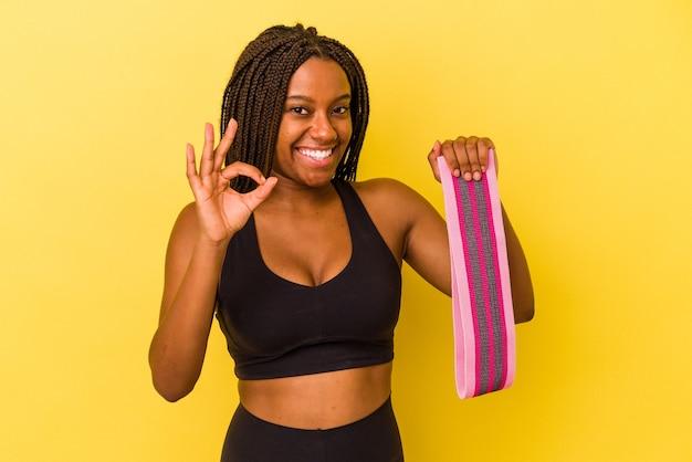 Mulher jovem esporte afro-americano segurando um elástico isolado em um fundo amarelo alegre e confiante, mostrando o gesto de ok.