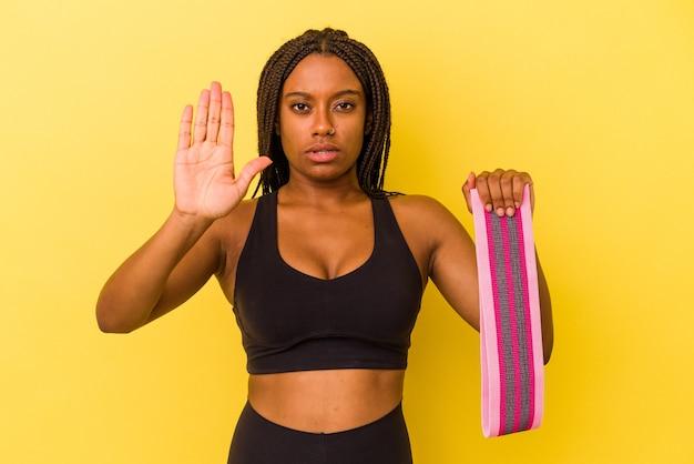 Mulher jovem esporte afro-americano segurando um elástico isolado em um fundo amarelo em pé com a mão estendida, mostrando o sinal de stop, impedindo-o.