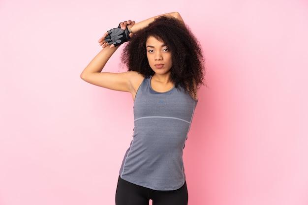 Mulher jovem esporte americano africano isolada no alongamento rosa