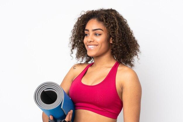Mulher jovem esporte americano africano na parede branca com uma esteira