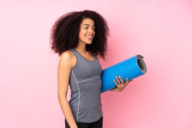 Mulher jovem esporte americano africano na parede rosa com uma esteira