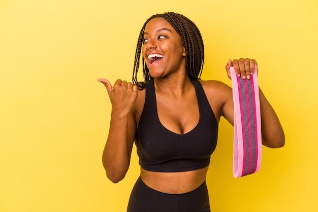 Mulher jovem esporte americano africano segurando um elástico isolado em pontos de fundo amarelo com o dedo polegar afastado, rindo e despreocupada.