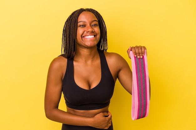 Mulher jovem esporte americano africano segurando um elástico isolado em um fundo amarelo, rindo e se divertindo.