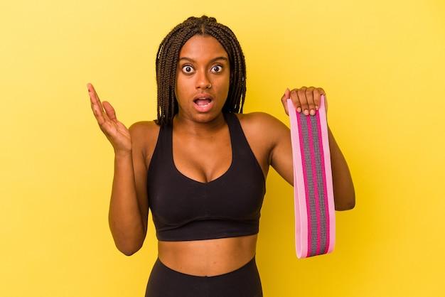 Mulher jovem esporte americano africano segurando um elástico isolado em um fundo amarelo surpreso e chocado.