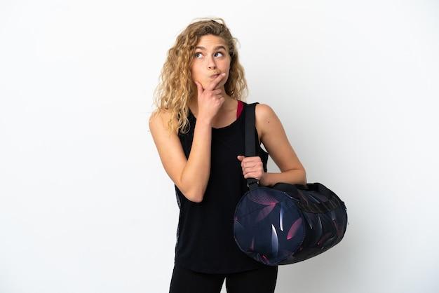 Mulher jovem esporte com bolsa esporte isolada no fundo branco, tendo dúvidas enquanto olha para cima