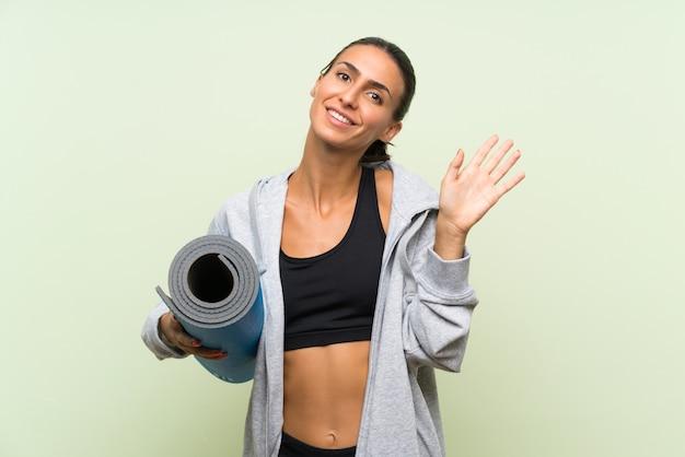 Mulher jovem esporte com esteira sobre parede verde isolada, saudando com a mão com expressão feliz