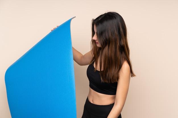 Mulher jovem esporte com esteira sobre parede