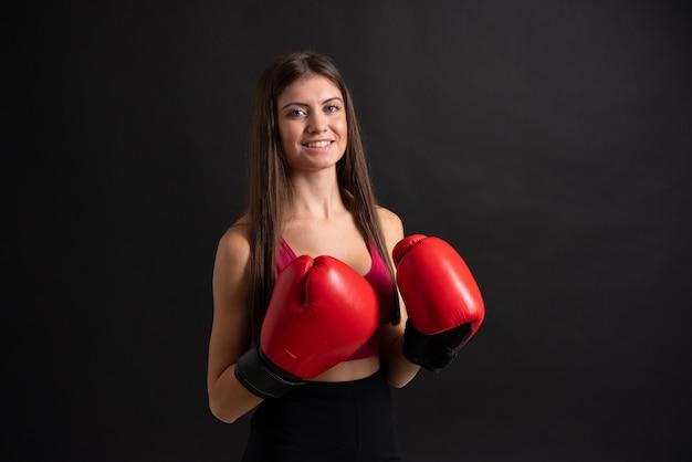 Mulher jovem esporte com luvas de boxe sobre fundo preto isolado