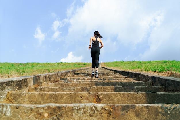 Mulher jovem esporte correndo ao ar livre no andar de cima no céu azul