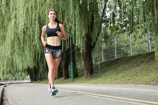 Mulher jovem esporte correndo no parque.