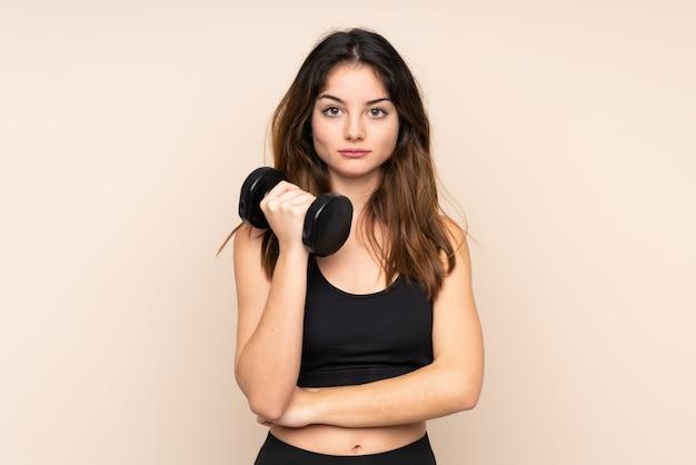 Mulher jovem esporte fazendo halterofilismo isolado em bege, mantendo os braços cruzados