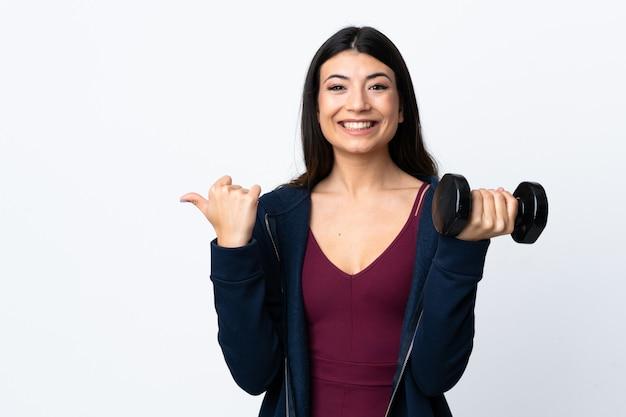 Mulher jovem esporte fazendo halterofilismo sobre parede branca isolada, apontando para o lado para apresentar um produto