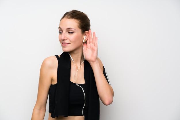 Mulher jovem esporte isolado parede branca ouvindo algo