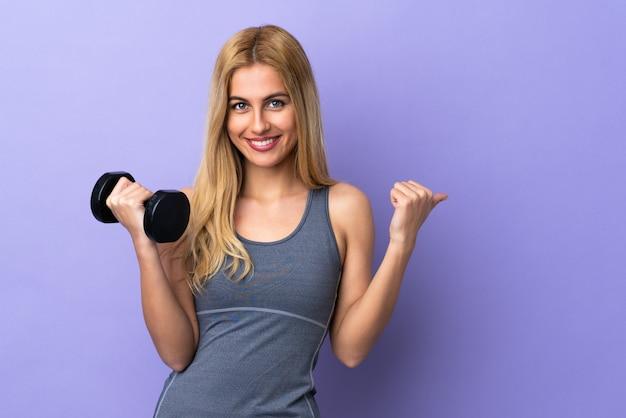 Mulher jovem esporte loira fazendo levantamento de peso isolado roxo apontando para o lado para apresentar um produto