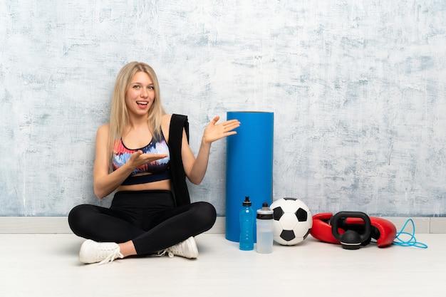 Mulher jovem esporte loira sentada no chão, estendendo as mãos para o lado