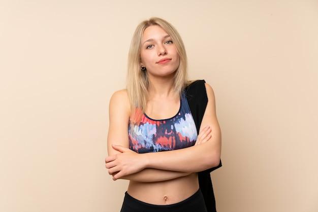 Mulher jovem esporte loira sobre parede isolada, mantendo os braços cruzados