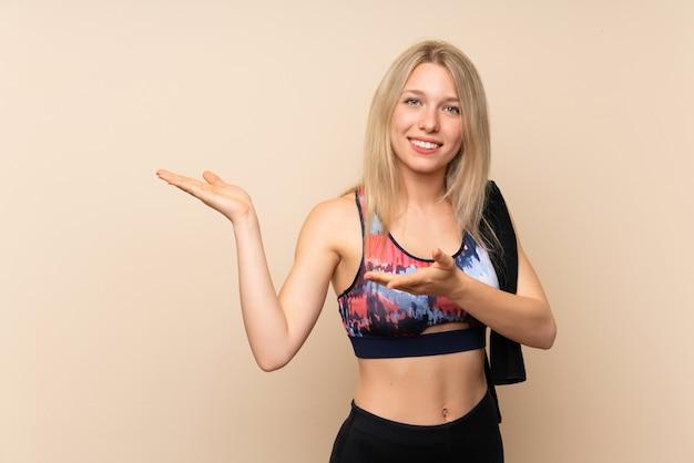 Mulher jovem esporte loiro sobre parede isolada, estendendo as mãos para o lado para convidar para vir