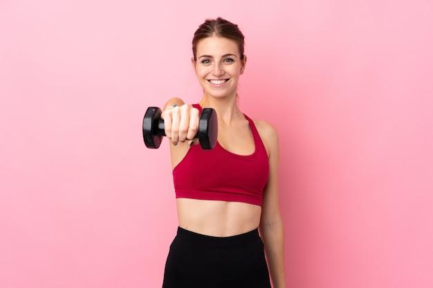Mulher jovem esporte parede isolada rosa fazendo levantamento de peso