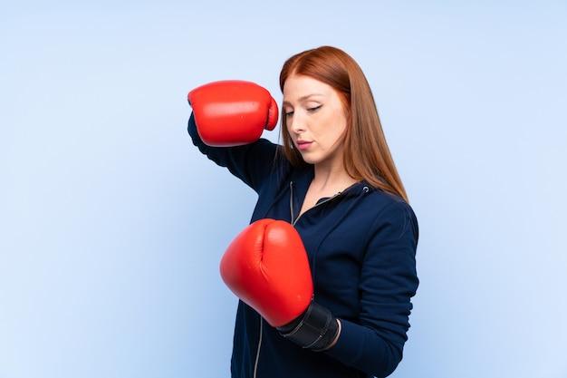Mulher jovem esporte ruiva sobre fundo azul isolado com luvas de boxe