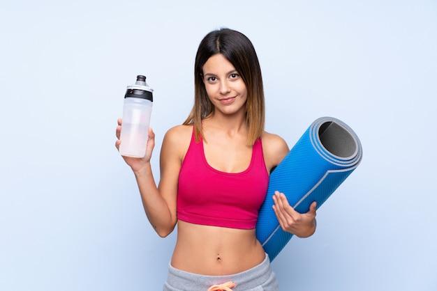 Mulher jovem esporte sobre parede azul isolada com garrafa de água de esportes e com uma esteira