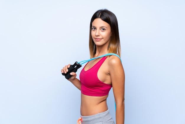 Mulher jovem esporte sobre parede azul isolada com pular corda