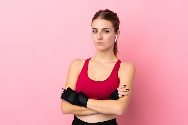 Mulher jovem esporte sobre parede rosa isolada, mantendo os braços cruzados