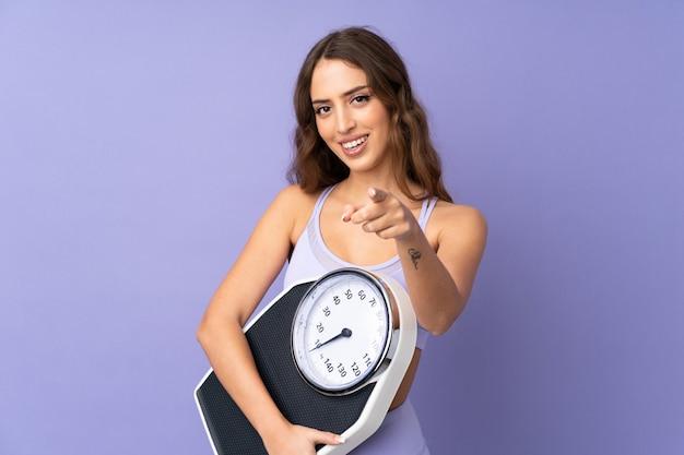 Mulher jovem esporte sobre parede roxa isolada, segurando uma máquina de pesagem e apontando para a frente