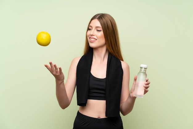 Mulher jovem esporte sobre parede verde isolada com uma maçã