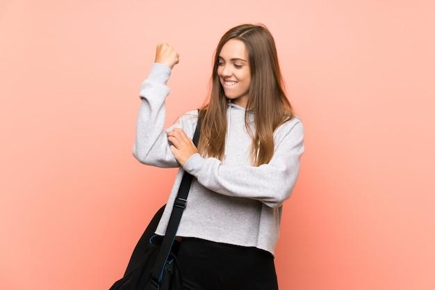 Mulher jovem esporte sobre rosa isolada fazendo gesto forte