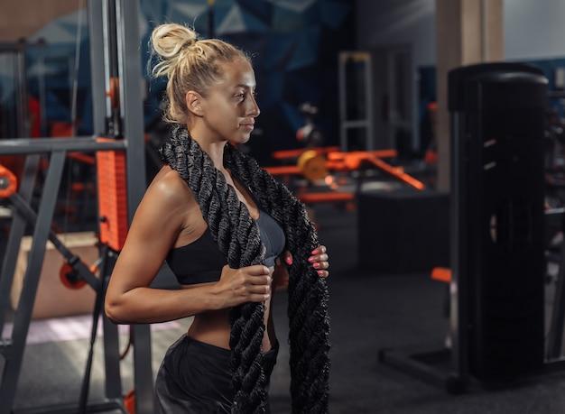Mulher jovem esporte sportswear com corda de batalha no pescoço no ginásio. treino funcional. conceito de estilo de vida saudável