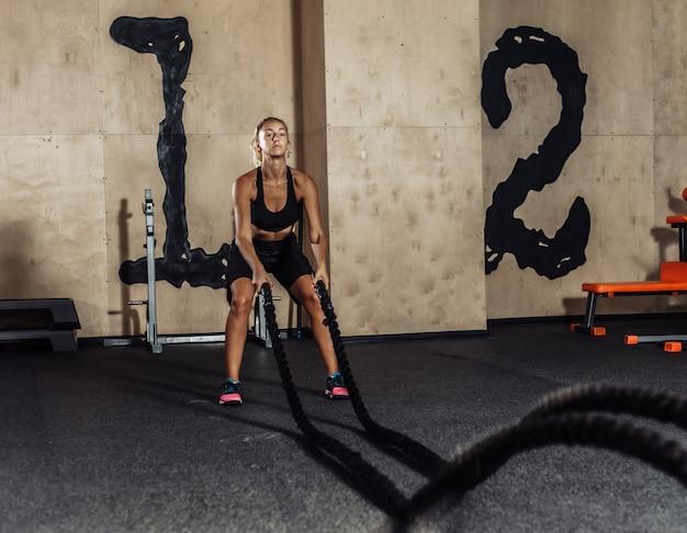 Mulher jovem esporte sportswear está treinando com corda de batalha no ginásio. treino funcional. conceito de estilo de vida saudável
