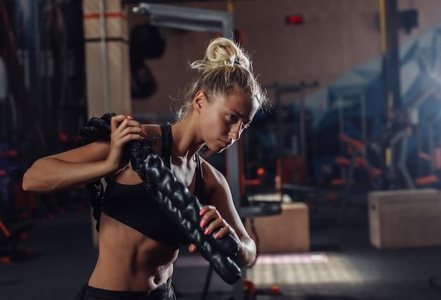 Mulher jovem esporte sportswear está treinando com corda de batalha nos ombros no ginásio. treino funcional. conceito de estilo de vida saudável