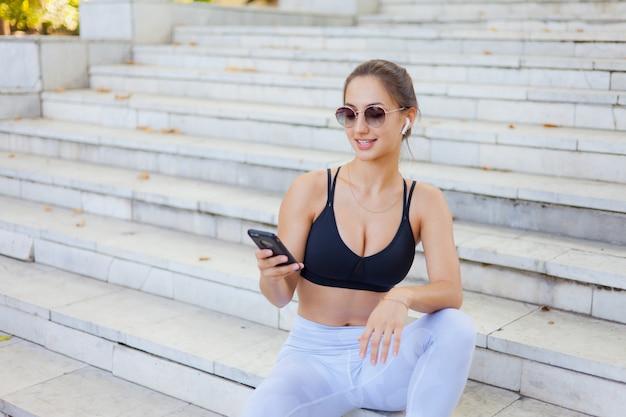 Mulher jovem esporte sportswear usar smartphone e ouve música em fones de ouvido enquanto está sentado na escada em dia ensolarado