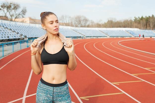 Mulher jovem esportes após treino com toalha nos ombros no estádio após treino de corrida