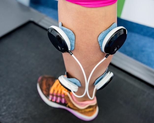 Mulher jovem esportes com eletroestimulador nos músculos das pernas.