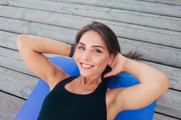 Mulher jovem esportes fazendo exercícios para os músculos abdominais, deitada na esteira em tábuas de madeira ao ar livre.