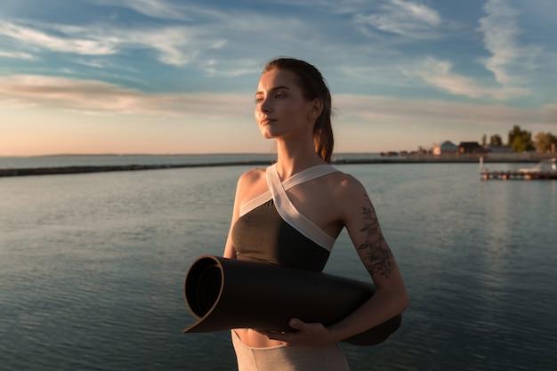 Mulher jovem esportes na praia em pé com tapete
