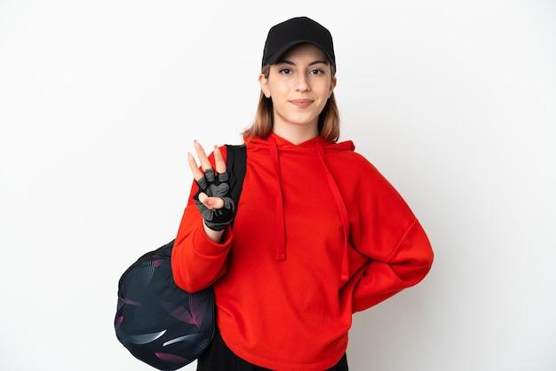 Mulher jovem esportiva com bolsa esportiva isolada no branco feliz e contando três com os dedos